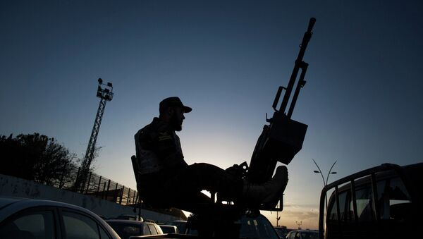 A Libyan army soldier stands guard sitting on an antiaircraft truck during the handover of the Nawaseen military compound, which was the headquarters of Libyan militias, in Souk al-Juma district, Tripoli, Libya - Sputnik Türkiye