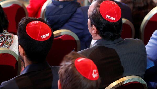 ABD Başkanı Donald Trump'ın Las Vegas'taki Cumhuriyetçi Yahudi Koalisyonu toplantısına hitabını dinlemeye gelenler arasında Yahudilerin dini takkesi kippayı Trump yazısı işlenmiş halde giyenler de vardı. - Sputnik Türkiye