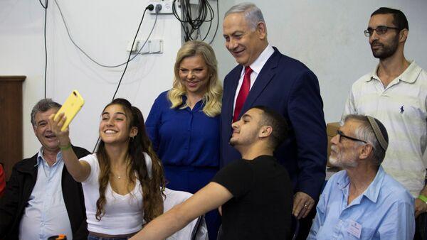 Sara-Benyamin Netanyahu çifti oy kullandıkları seçim merkezinde gençlerle selfie çektirdi. - Sputnik Türkiye