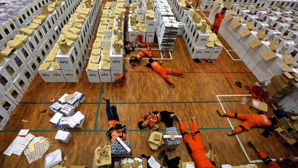 Endonezya'daki dünyanın en büyük tek günlük seçimi öncesinde, sandık materyallerini hazırlayan işçiler başkent Jakarta'da mola sırasında dinleniyor. - Sputnik Türkiye