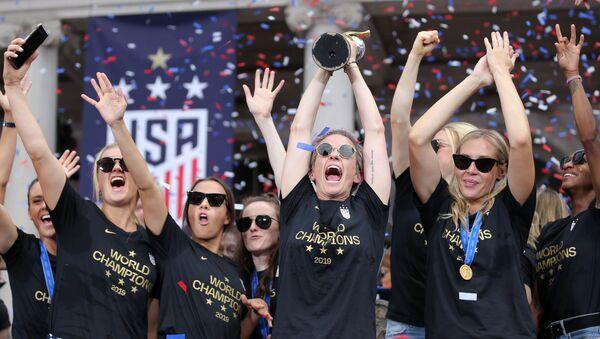 ABD kadın futbol milli takımı kaptan Megan Rapinoe'nin elindeki Dünya Kupası ile geri döndüğü New York'ta kahraman gibi karşılanırken - Sputnik Türkiye