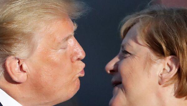 Fransa'nın Biarritz kentindeki G7 zirvesinin aile fotoğrafı çekimi sırasında ABD Başkanı Trump sık sık sert şekilde eleştirdiği Almanya Başbakanı Merkel'i 'yavaş çekimle' yanağından öptü. - Sputnik Türkiye