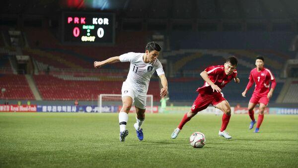 15 Ekim 2019'da Pyongyang'ın Kim Il Sung Stadyumu'nda oynanan Kuzey ile Güney Kore arasındaki maçta Güneyli Hwang Hee-chan topla hücumda - Sputnik Türkiye