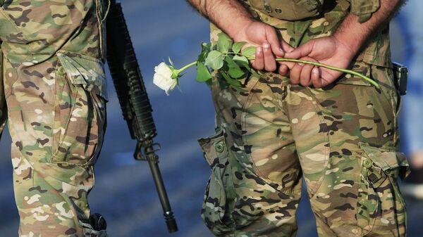 Halk ülkedeki ekonomik durumu protesto ederken, Lübnan askeri elinde beyaz bir çiçek taşıyor. - Sputnik Türkiye