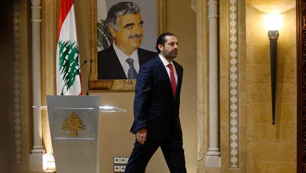Suikasta kurban giden babası Refik Hariri'nin portresi önünde başbakanlıktan istifasını sunacağını açıklayan Saad Hariri, salondan çıkarken - Sputnik Türkiye