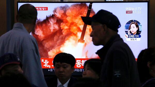 Kuzey Kore'nin Japon Denizi üzerinde balistik füze denemesi olduğu sanılan iki cisim fırlatmasıyla ilgili TV haberlerini takip eden Güney Koreliler  - Sputnik Türkiye