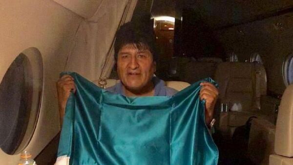 İstifaya zorlanan Bolivya Devlet Başkanı Evo Morales, iltica teklifini kabul ettiği Meksika hükümetinin uçağında ülkenin bayrağını taşırken. - Sputnik Türkiye