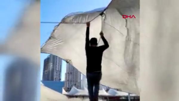 Kadıköy'de pazarcı çadır kurarken ip koptu. Şiddetli, rüzgar nedeniyle havalanan çadırın ipini bırakamayan pazarcı metrelerce yükseldi. O anlar cep telefonu kamerasına yansıdı. - Sputnik Türkiye