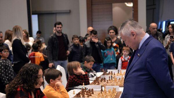 Mersin'deki Satranç Festivali'nde, 7 dünya şampiyonluğu bulunan Büyük Usta (Grand Master) Anatoly Karpov (sağda) ile berabere kalan 12 yaşındaki Işıl Cingöz (solda), büyük sevinç yaşadı. - Sputnik Türkiye