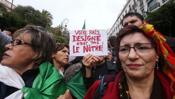 Cezayir'de seçim sonucu ve yeni devlet başkanının açıklanmasının ardından sokaklara dökülenler arasında Sizin devlet başkanınız bizim değil dövizi taşıyan grup - Sputnik Türkiye