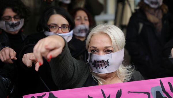 Şili'de başlayan ve dünyanın her yerinde kadına karşı şiddete dikkati çekmek için yapılan 'Las Tesis' eyleminin Tecavüzcü sizsiniz sözünü pankart olarak açan Kıbrıslı kadın aktivistler,kimliğinin saklı kalması için yüzü kapatılarak mahkemeden çıkarılan Britanyalı genceSeninle birlikteyiz, Sana inanıyoruz diye bağırdı. - Sputnik Türkiye