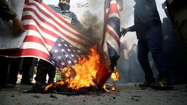 Kudüs Gücü Komutanı Kasım Süleymani'nin öldürülmesinin ardından gerçekleştirilen protestolarda ABD ve İngiltere bayrakları ateşe verildi. - Sputnik Türkiye