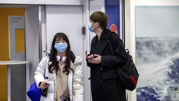 Koronavirüs salgınının çıktığı Çin'in Vuhan kentinden Finlandiya'nın Ivalo Havaalanı'na inen turistler - Sputnik Türkiye
