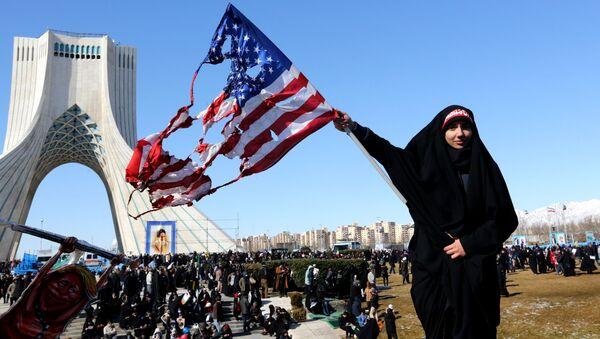 Tahran'daki Azadi Meydanı'nda İran İslam Devrimi 41. yıldönümü törenleri sırasında bir kadın yanmış ABD bayrağı sallarken - Sputnik Türkiye