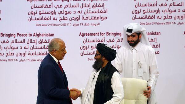 ABD - Taliban barış anlaşmasını imzalayan ABD'nin Özel Temsilcisi Zalmay Halilzad ve Taliban Siyasi Ofisi Direktörü Molla Abdul Gani Baradar - Sputnik Türkiye