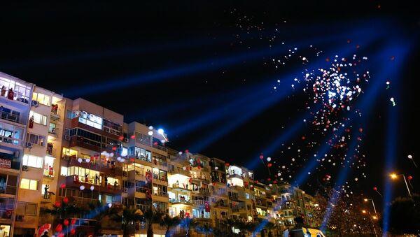 İzmir'de vatandaşlar, yeni tip koronavirüse (Kovid-19) karşı alınan tedbirler kapsamında, TBMM Başkanı Mustafa Şentop'un çağrısı üzerine 23 Nisan Ulusal Egemenlik ve Çocuk Bayramı ile TBMM'nin açılışının 100. yılını evlerinin balkonlarından ve pencerelerinden saat 21:00'da ay yıldızlı bayraklar eşliğinde İstiklal Marşını okuyarak kutladı. Kutlamalar çerçevesinde Kadifekale'den havai fişek gösterisi yapıldı. - Sputnik Türkiye