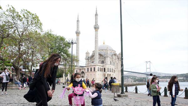 İstanbul'da yeni tip koronavirüs (Kovid-19) nedeniyle sokağa çıkmaları kısıtlanan 14 yaş altı çocuklar, 11.00-15.00 saatlerinde getirilen serbestlik ile uzun bir aradan sonra dışarı çıktı. Ortaköy'e aileleriyle gelen çocuklar oyun oynadı. - Sputnik Türkiye