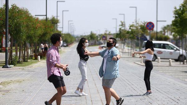 Antalya'da, yeni tip koronavirüs (Kovid-19) tedbirleri kapsamında getirilen sokağa çıkma kısıtlaması 4 saatliğine kaldırılan 15-20 yaş grubundaki gençler, uzun aradan sonra dışarıda olmanın keyfini yaşadı. Bir grup genç, dünyaca ünlü Konyaaltı Sahili'nin Kovid-19 tedbirleri kapsamında trafiğe kapatılan çift şeritli yolunda Erik Dalı şarkısı eşliğinde oynadı. - Sputnik Türkiye