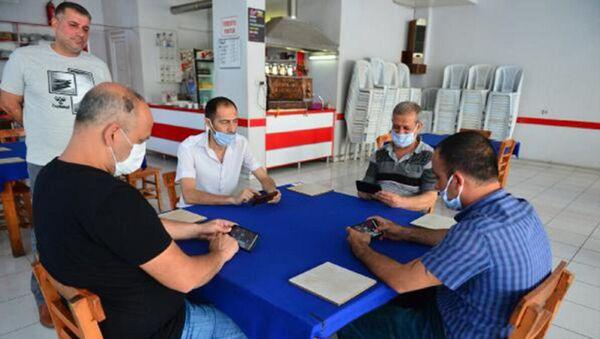 Adana'da okey, tavla, iskambil oynanmaması kaydıyla açılan kahvehaneye gelen vatandaşlar, cep telefonlarındaki uygulamayla mobil okey oynadı. - Sputnik Türkiye