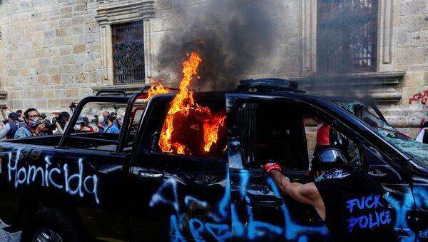 Meksika'da bir kişinin polis şiddetiyle öldürüldüğü iddiasıyla başlayan protestolardagöstericiler, bir polisi ateşe verdi. - Sputnik Türkiye