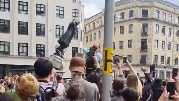 İngiltere'nin Bristol kentinde ırkçılık karşıtı gösteri düzenleyenler bir köle tacirinin heykelini yıktı. - Sputnik Türkiye