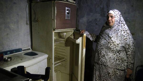 Lübnan'da AFP'nin ziyaret ettiği Sayda kenti sakini bir kadın, buzdolabını açarak içinin bomboş olduğunu gösterdi. - Sputnik Türkiye